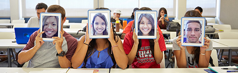 Four students sitting in a classroom playing around with iPads.