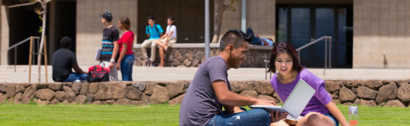 Two students share a moment on a laptop while sitting on the UH West Oahu's great lawn.