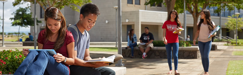 A couple reading textbooks in the UH West Oahu courtyard.