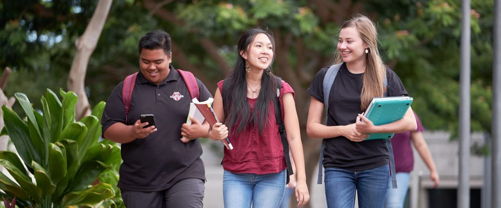 Three students walking in the courtyard.