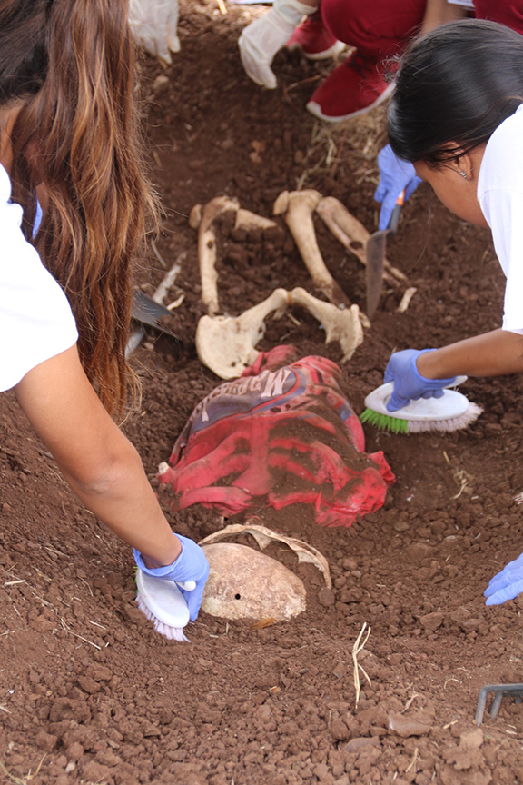 Students unearthing a fake corpse
