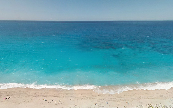Vast panoramic of a white sand beach with deep blue water
