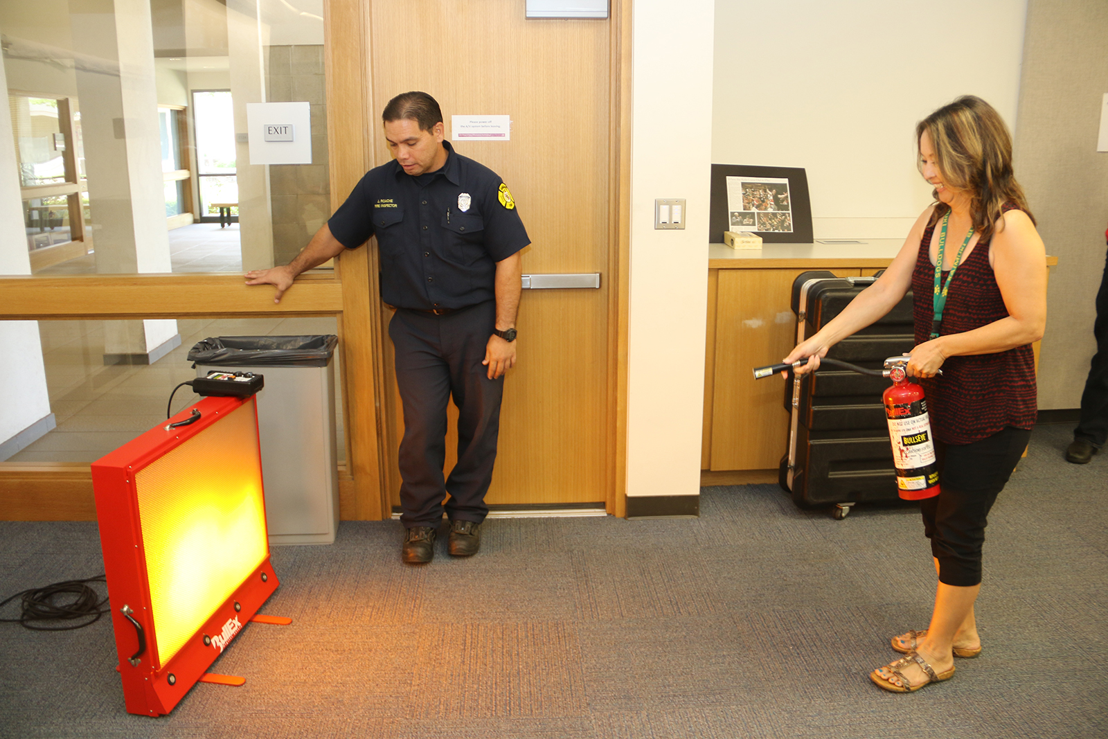 UHWO Human Resources Director Nancy Nakasone extinguishing a simulated flame during fire safety training.