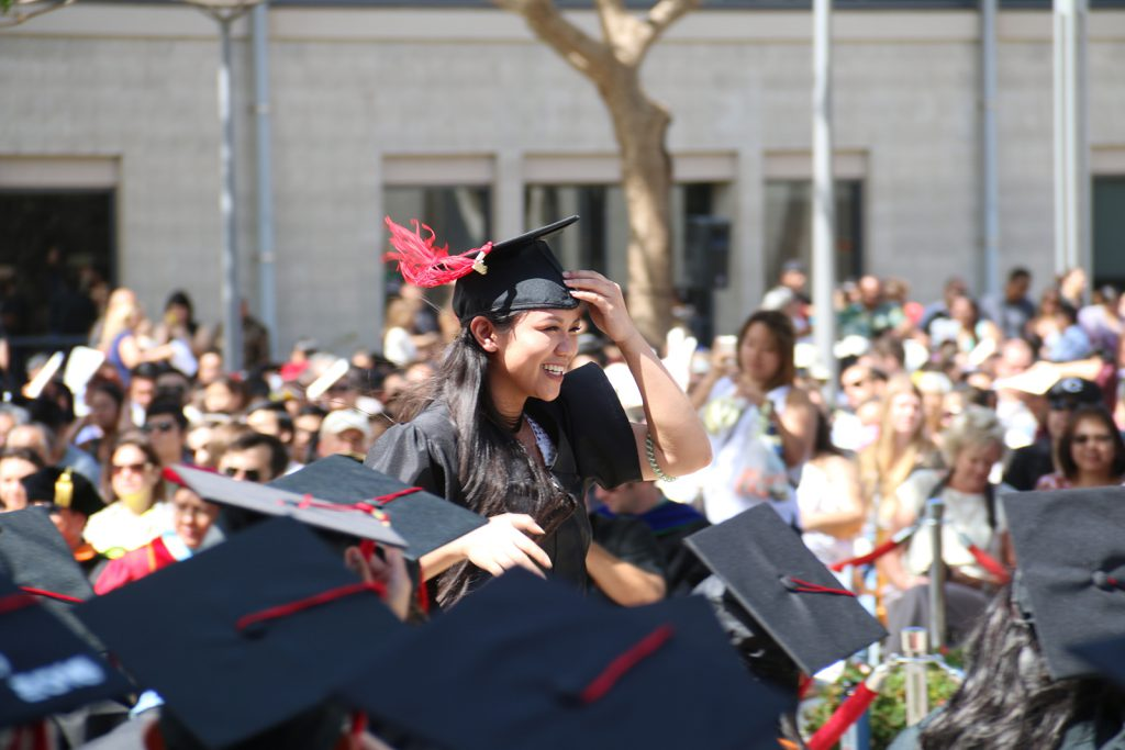 A happy UH West Oʻahu graduate smiles as she walks to receive her diploma from Interim Chancellor Doris Ching at the spring 2016 commencement.