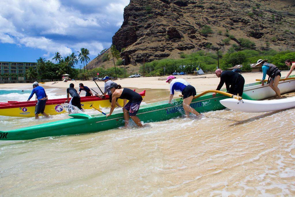 UH West Oʻahu faculty and staff learning how to paddle a canoe at Mākaha Beach during Pili ʻĀina in August 2014.