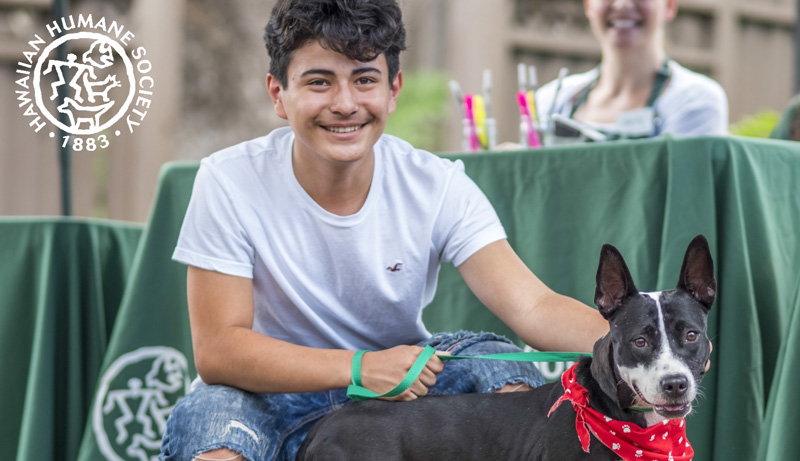 A boy and his dog squatting in front of a Hawaiian Humane Society outreach table.