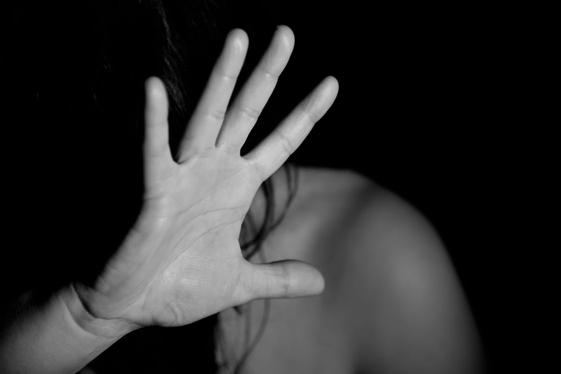 Dark photo of woman with hand up, shielding herself