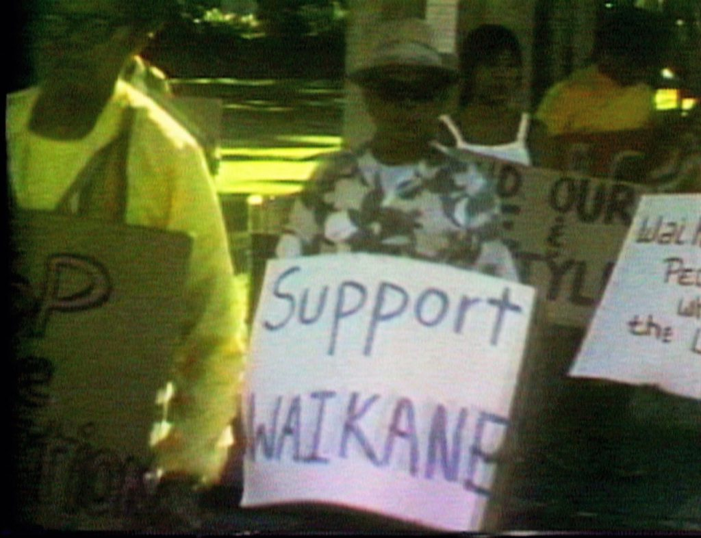Video frame grab of protester carrying sign saying Support Waikane