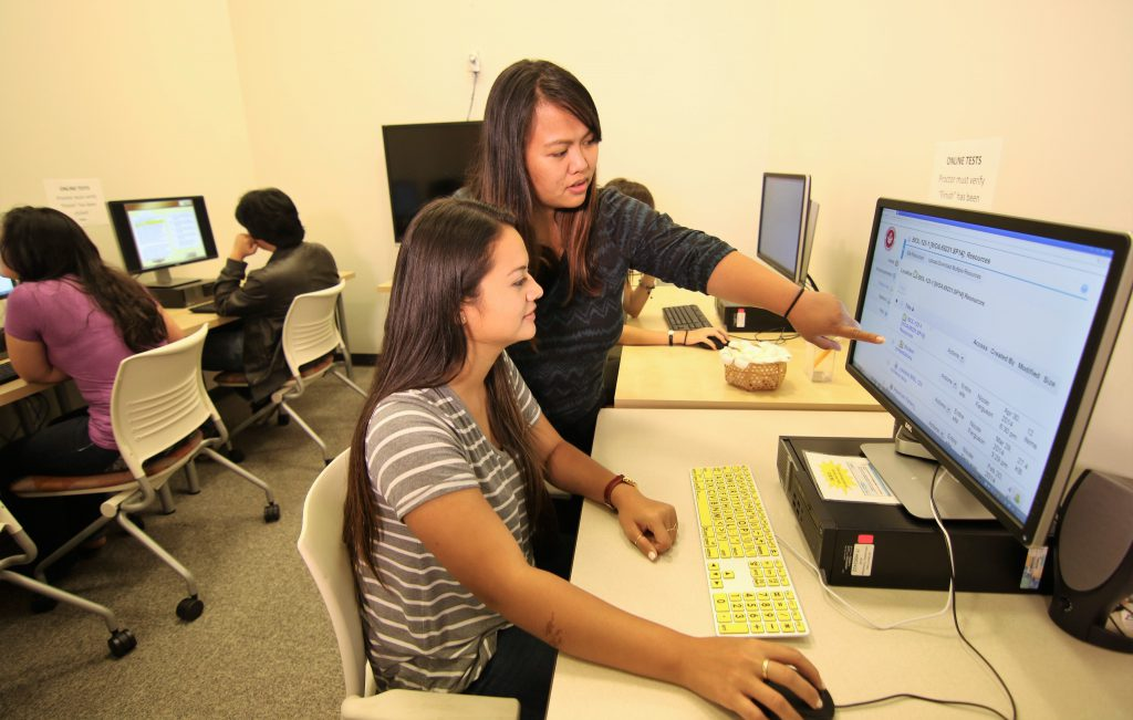 Caption to photo of students working at computer screen: No'eau Center staff will provide tutoring services on Kauaʻi and Maui next week.