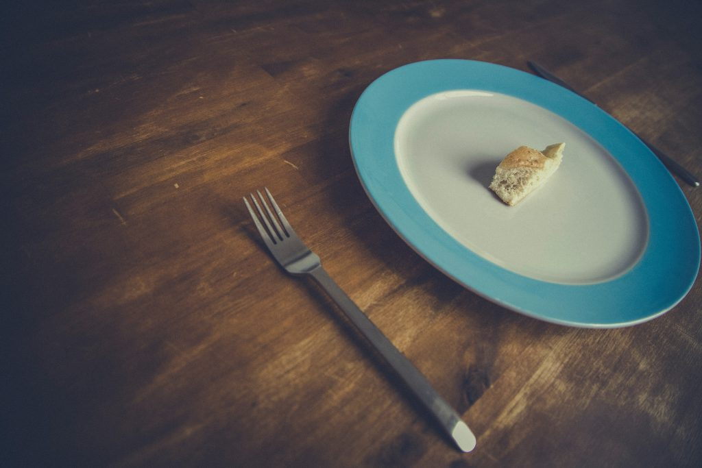 photo of a dinner plate with small piece of bread on it