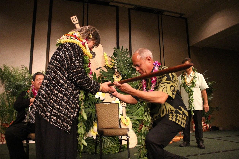 Photo of Giugni receiving award with caption Giugni recieves 'Ō'ō Award from Rick Fernandez, NHCC president
