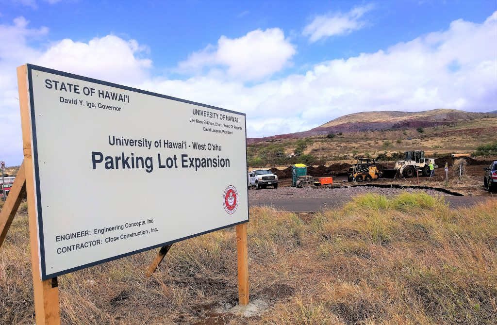 Photo of sign announcing parking lot expansion in foreground, vehicles and worksite in background