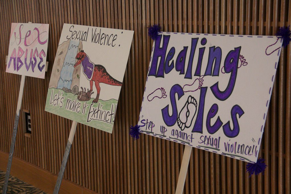 Three signs resting against the wall carrying the Healing Soles message about stepping up against sexual violence