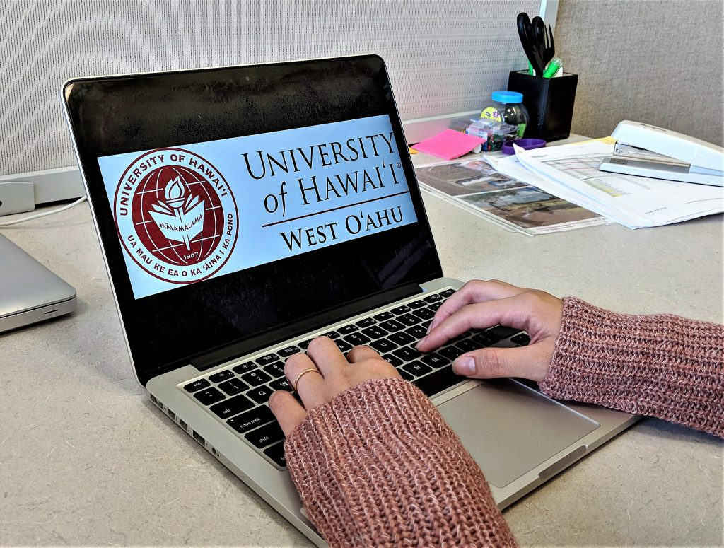 photo of someone's hands typing on a laptop with UHWO logo on the screen