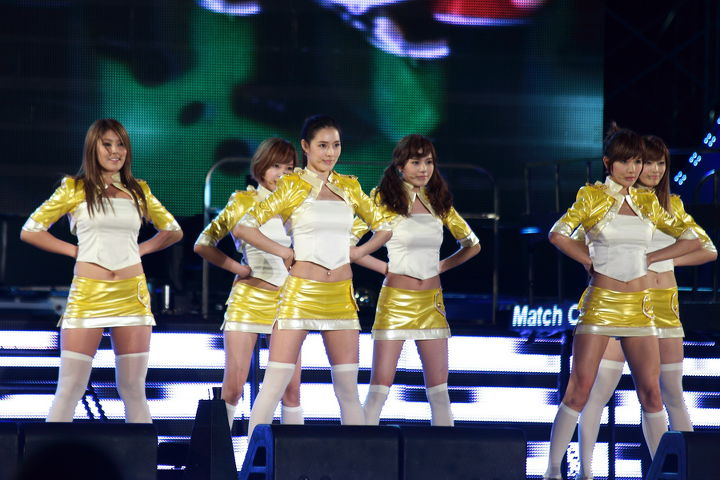 Photo of a K-Pop Girl group performing on stage dressed in yellow and white dresses