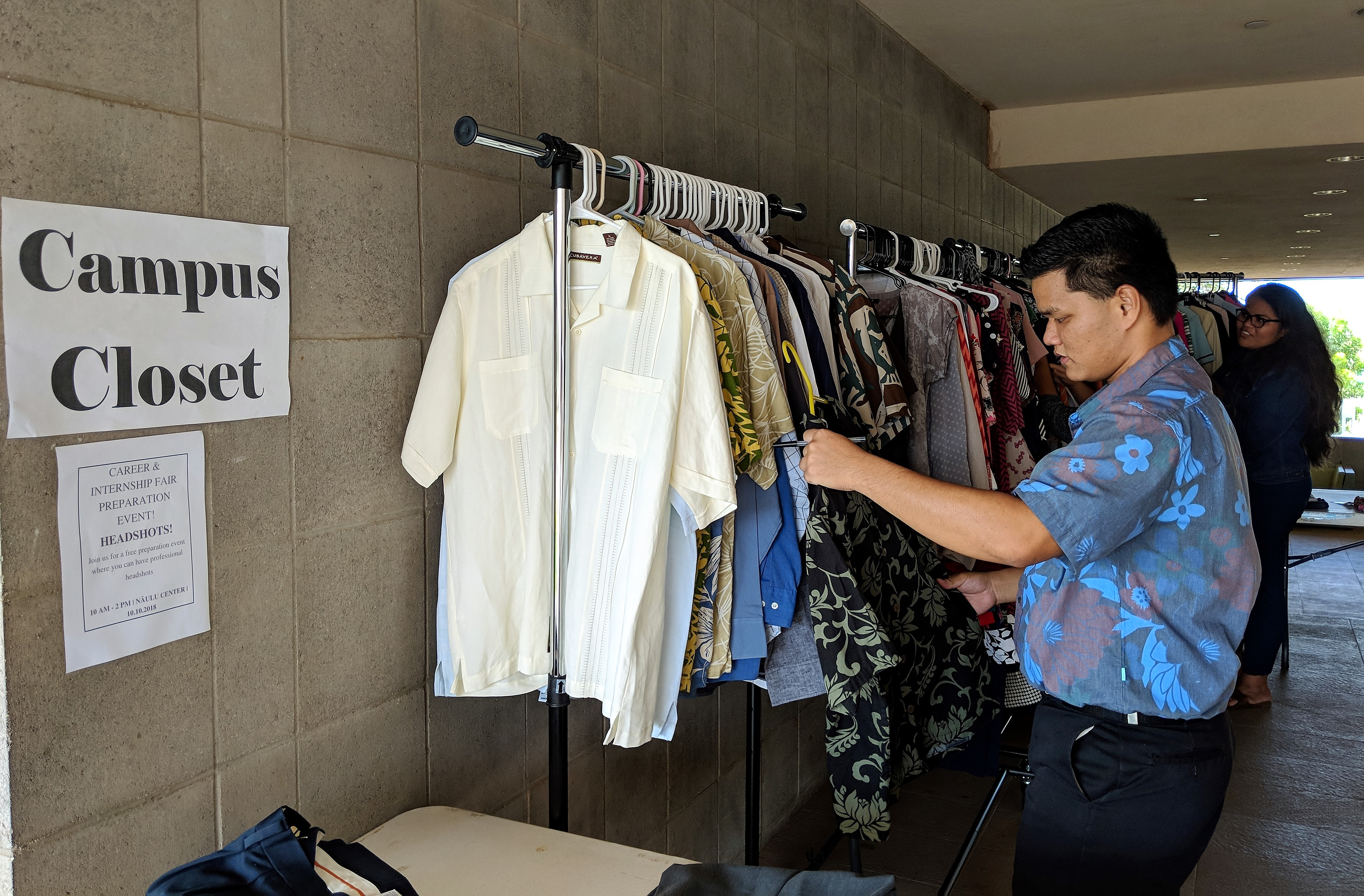Photo of a wall with Career Closet sign and a student looking at a shirt in front of a rack of shirts