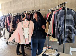 Shot of racks of clothes against a wall and two female students looking at a pink suit