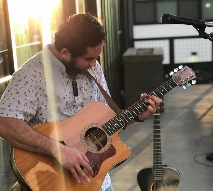 Shot of Danny Carvalho standing against some windows at sunset while playing a guitar. The sun is reflected off of the windows