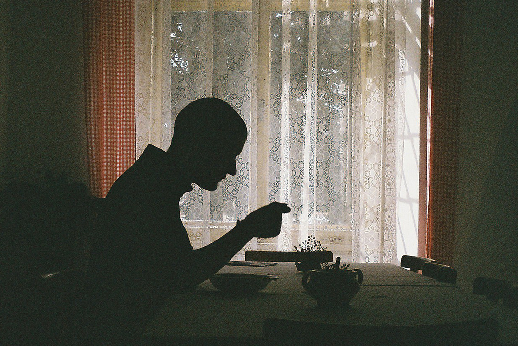 Silhouette of a man sitting at a table with bowl in front of him