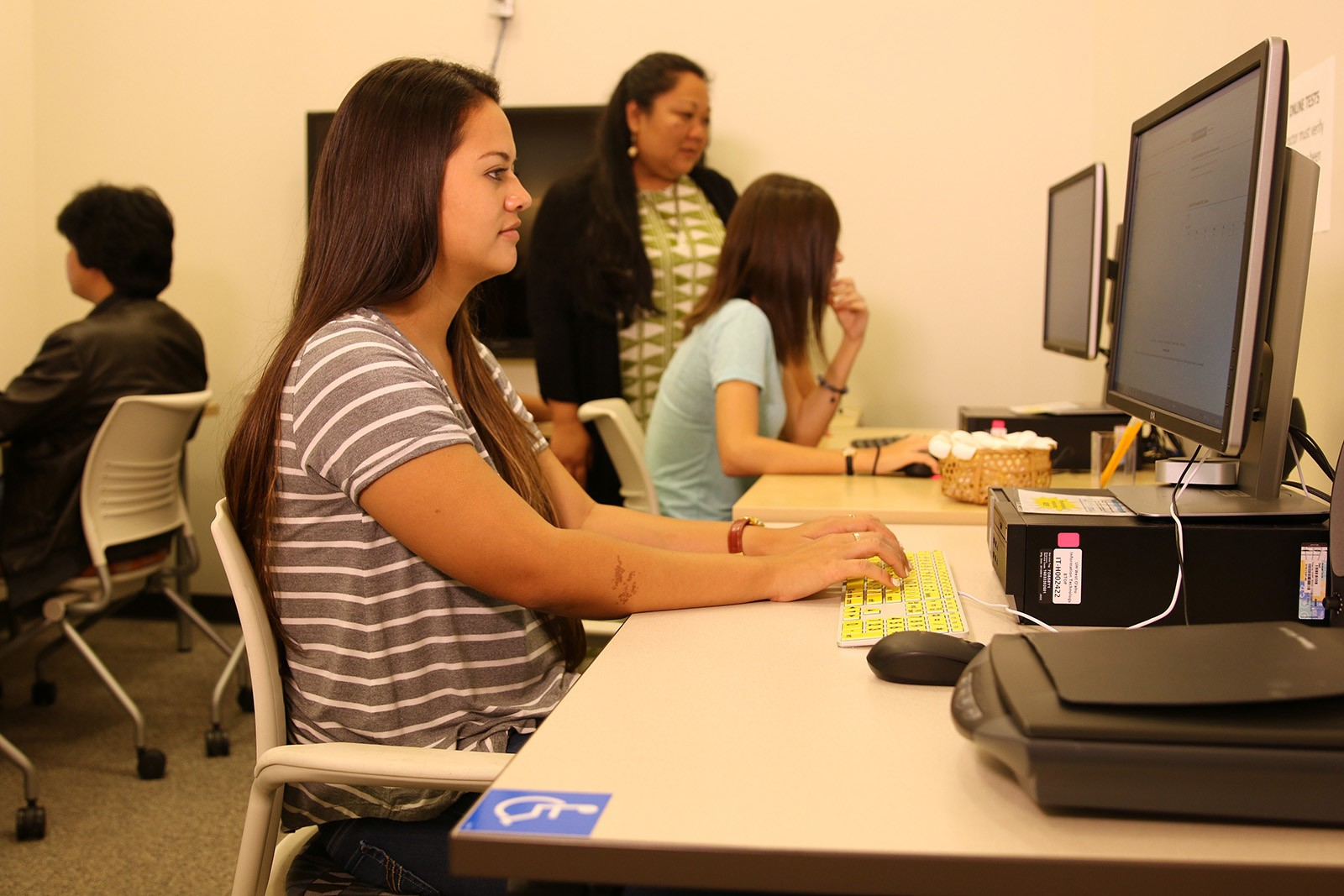Photo of two people taking tests at desktop computers with a test proctor in the background