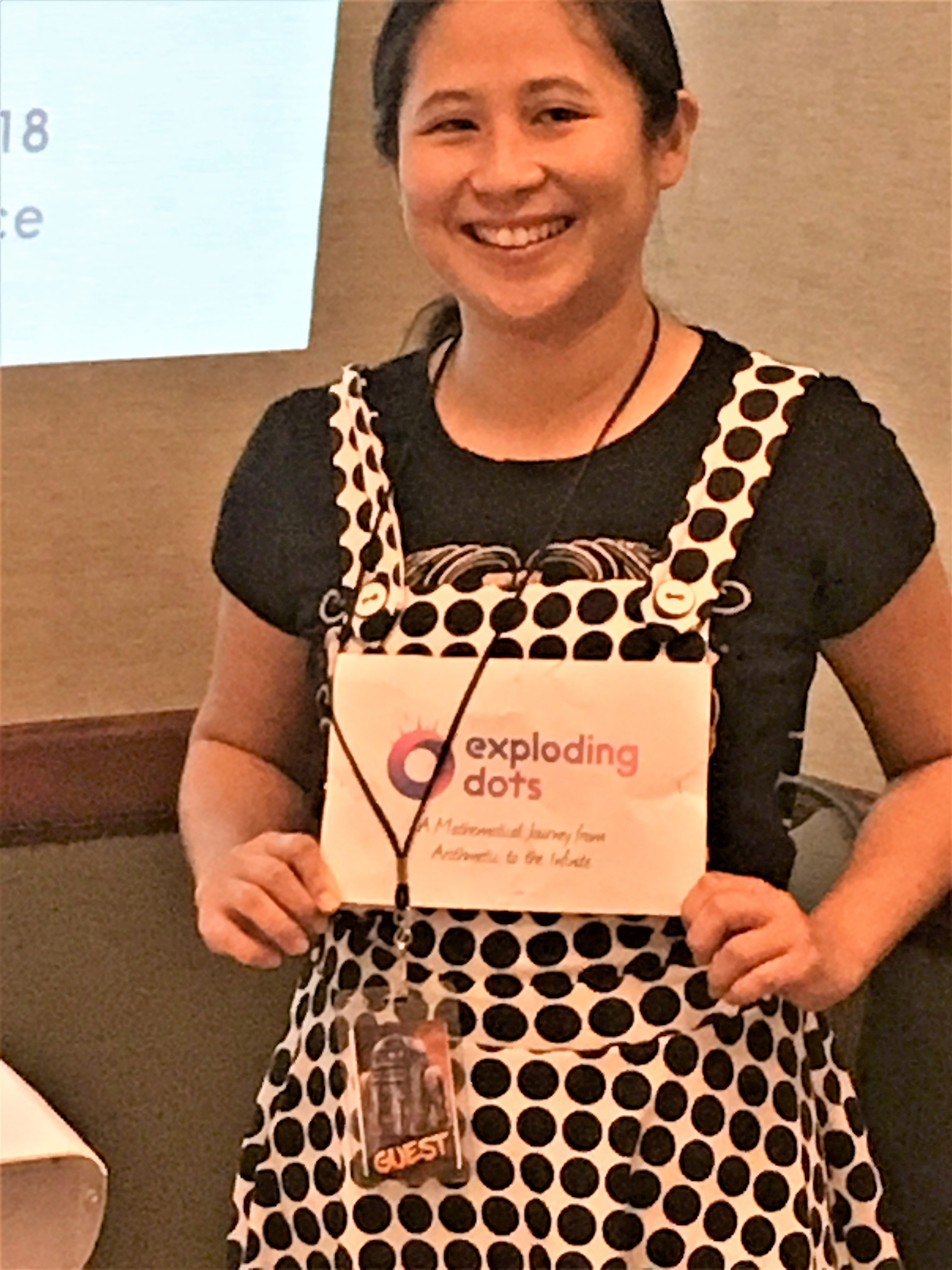 photo of Dr. Veny Liu wearing a polka-dot dress and sign saying Exploding Dots