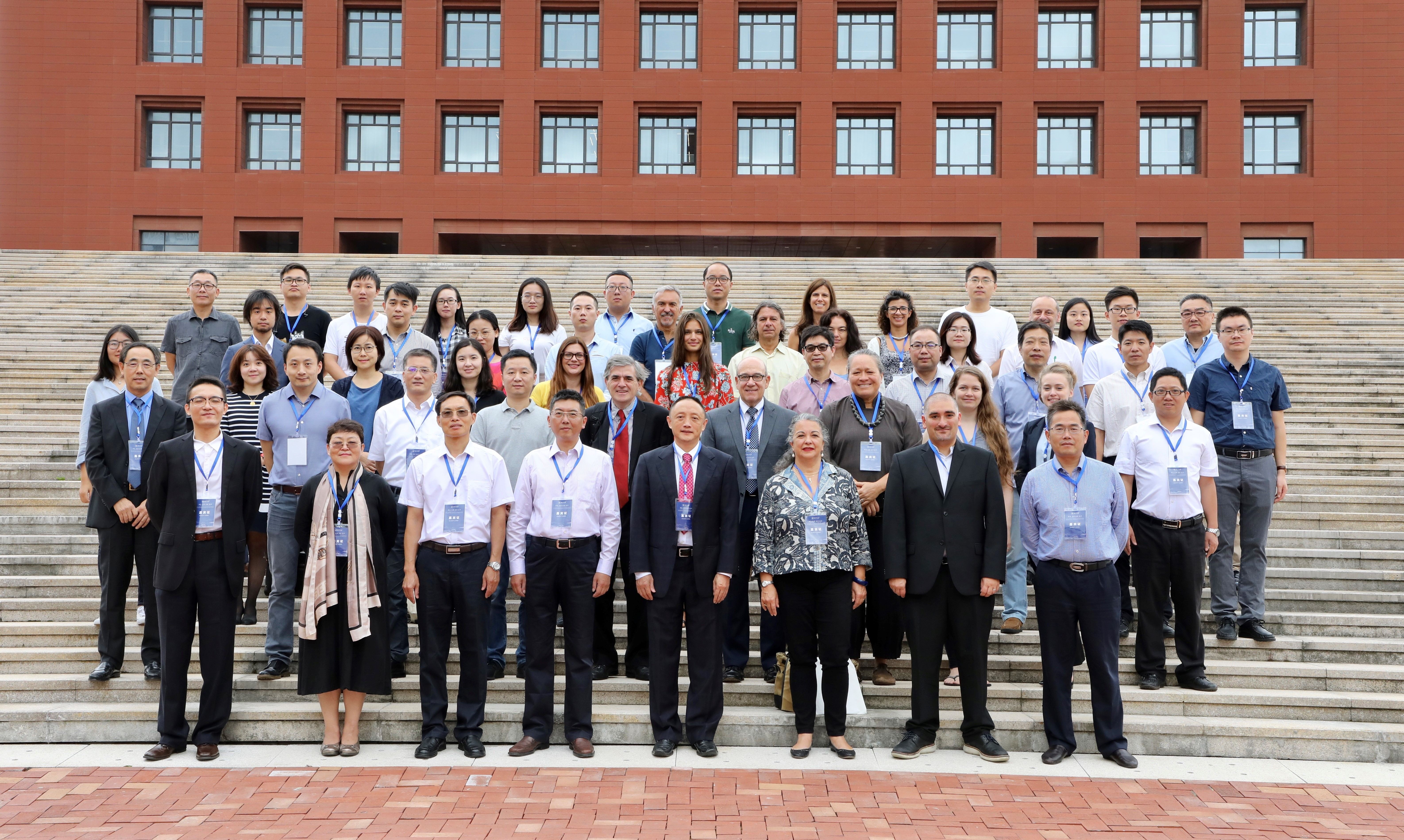 Photo of conference participants standing for an official photo on stairs in front of a brick building