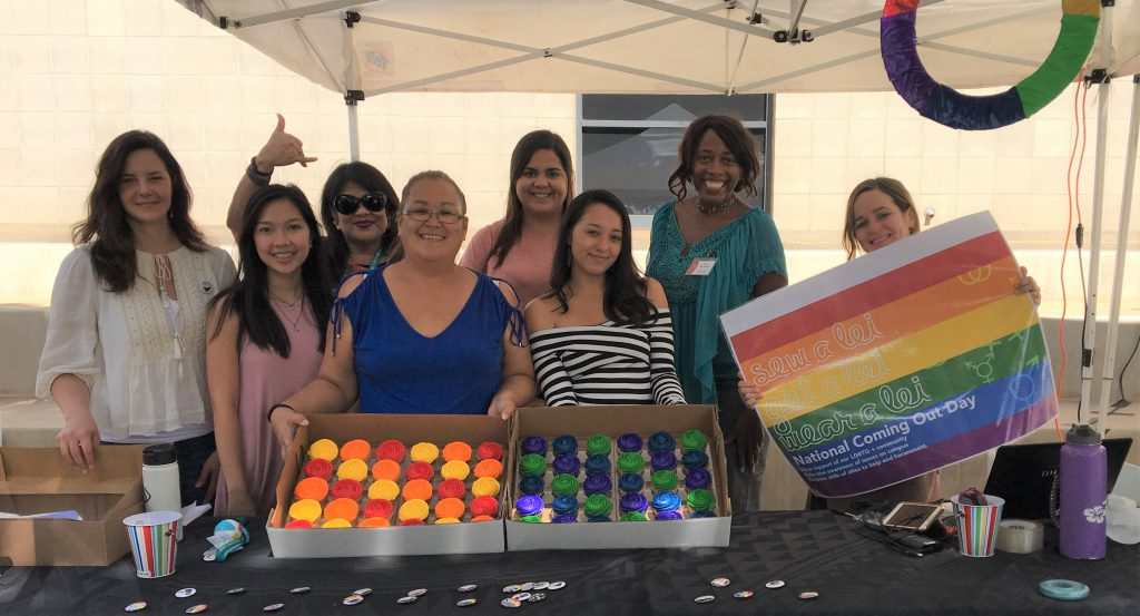 Photo of seven women at a table with multi-colored cupcakes and buttons