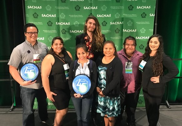 photo of five students and two faculty members posing in front of a screen that says SACNAS