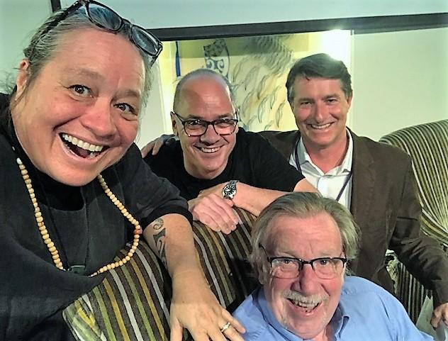 Selfie photo of Manu Aluli-Meyer with three gentlemen, one of whom is sitting