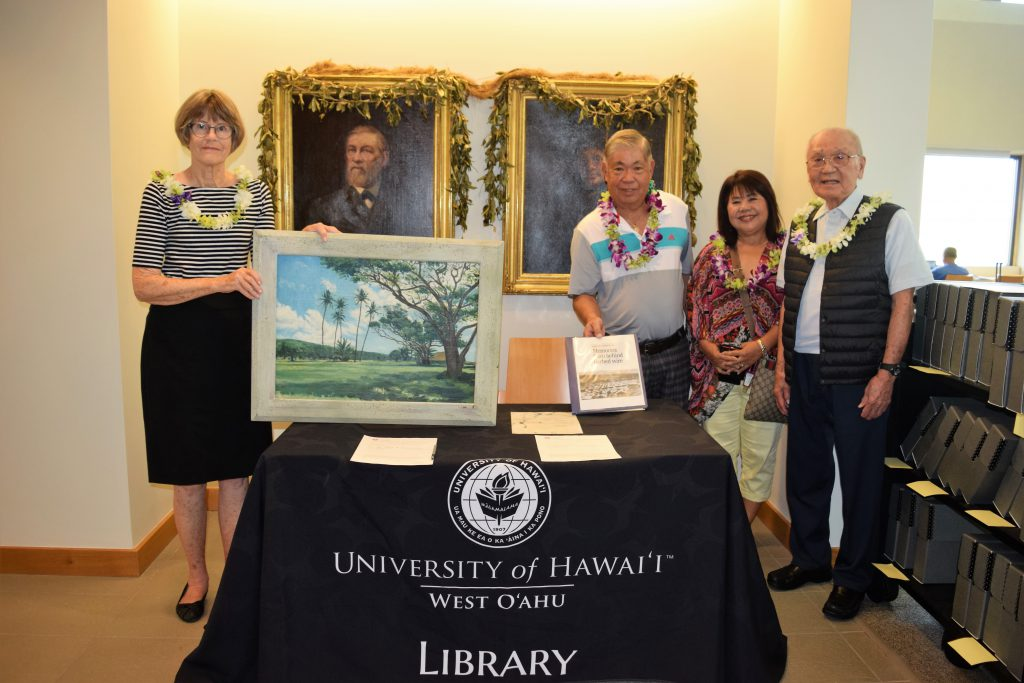 photo of four people standing behind a table. Woman on the left, Letitia Hickson is holding up a painting she donated, while to the right of her Ronald Ikehara holds up a notebook containing letters from POWs