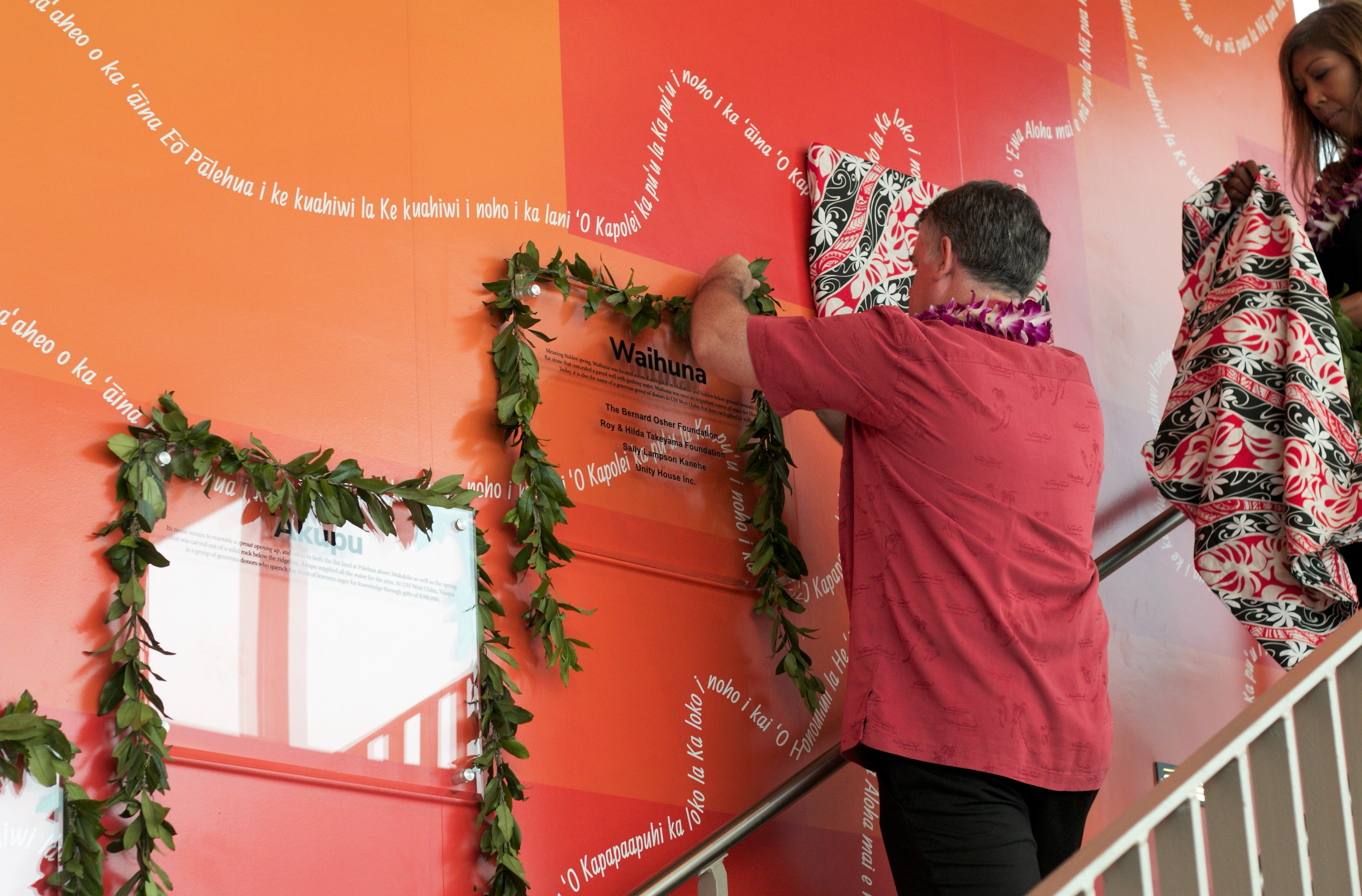 Shot of Kent Coarsey draping one of the clear plaques with a maile lei while standing on a staircase before the donor wall
