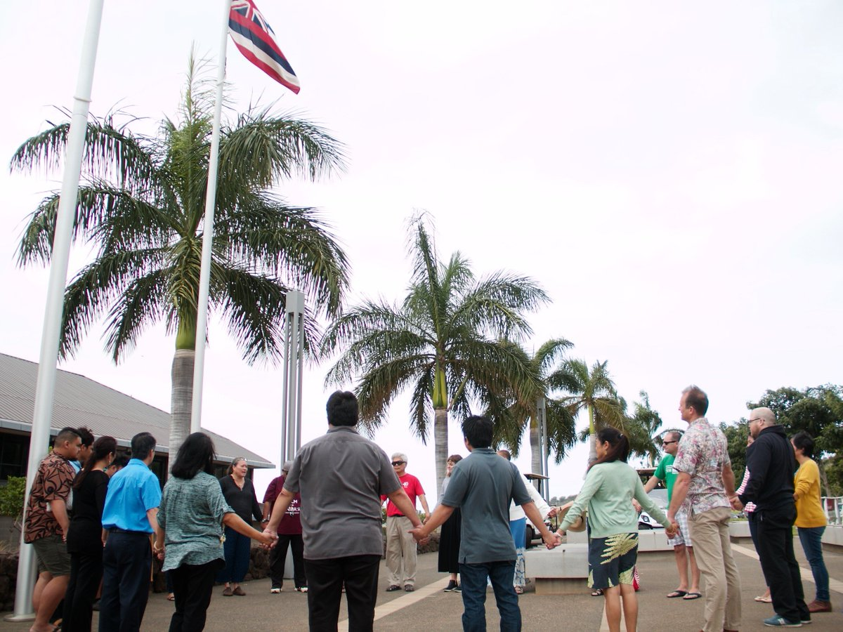 photo of people standing in a circle, holding hands, with Hawaiian flag flying above them