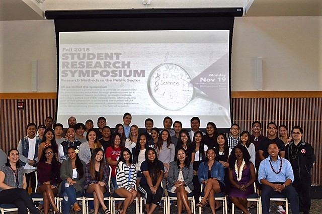 Photo of dozens of people posed for a picture in front of a screen that has the words Student Research Symposium