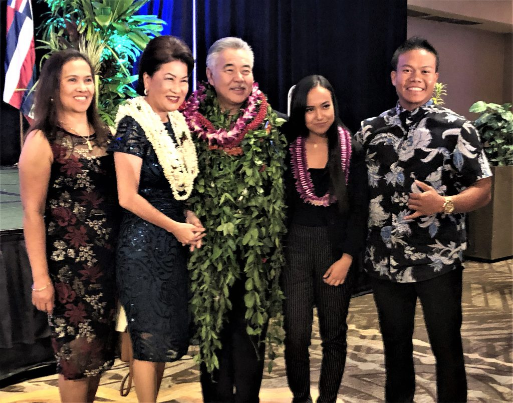 photo of five people standing for a photo. Three of them (Dawn and David Ige and Villanueva) are wearing lei.