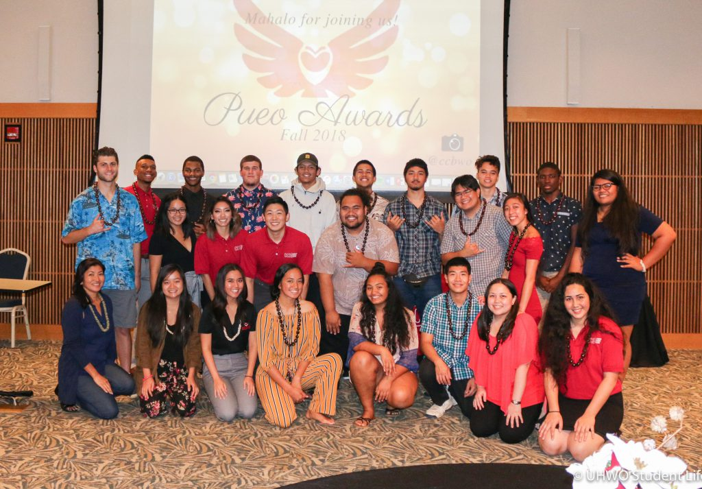 Photo of students standing and kneeling in a group picture with a screen illuminated with the words Pueo Awards in the background