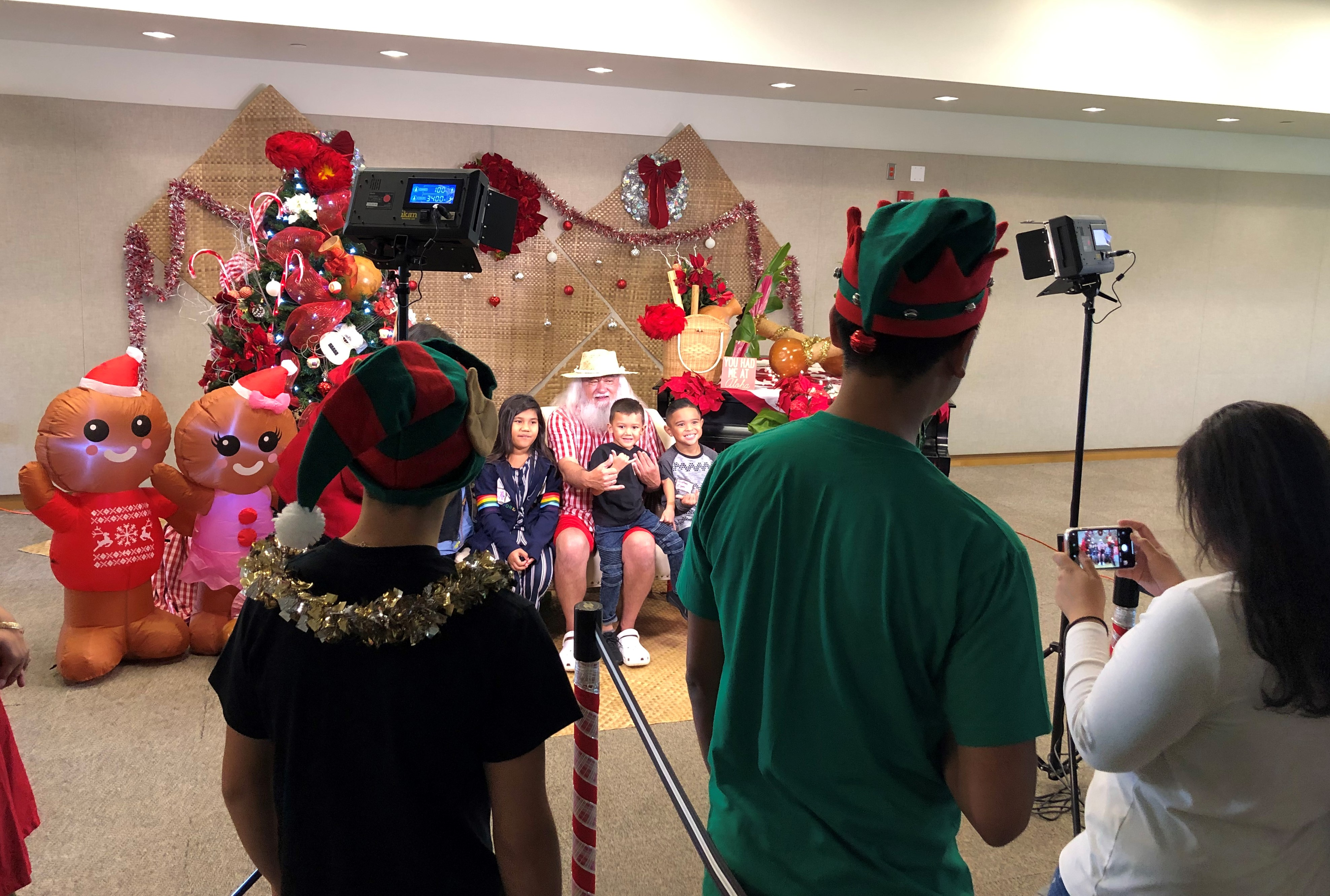Photo of children sitting with Santa in shorts being photographed and watched by other people