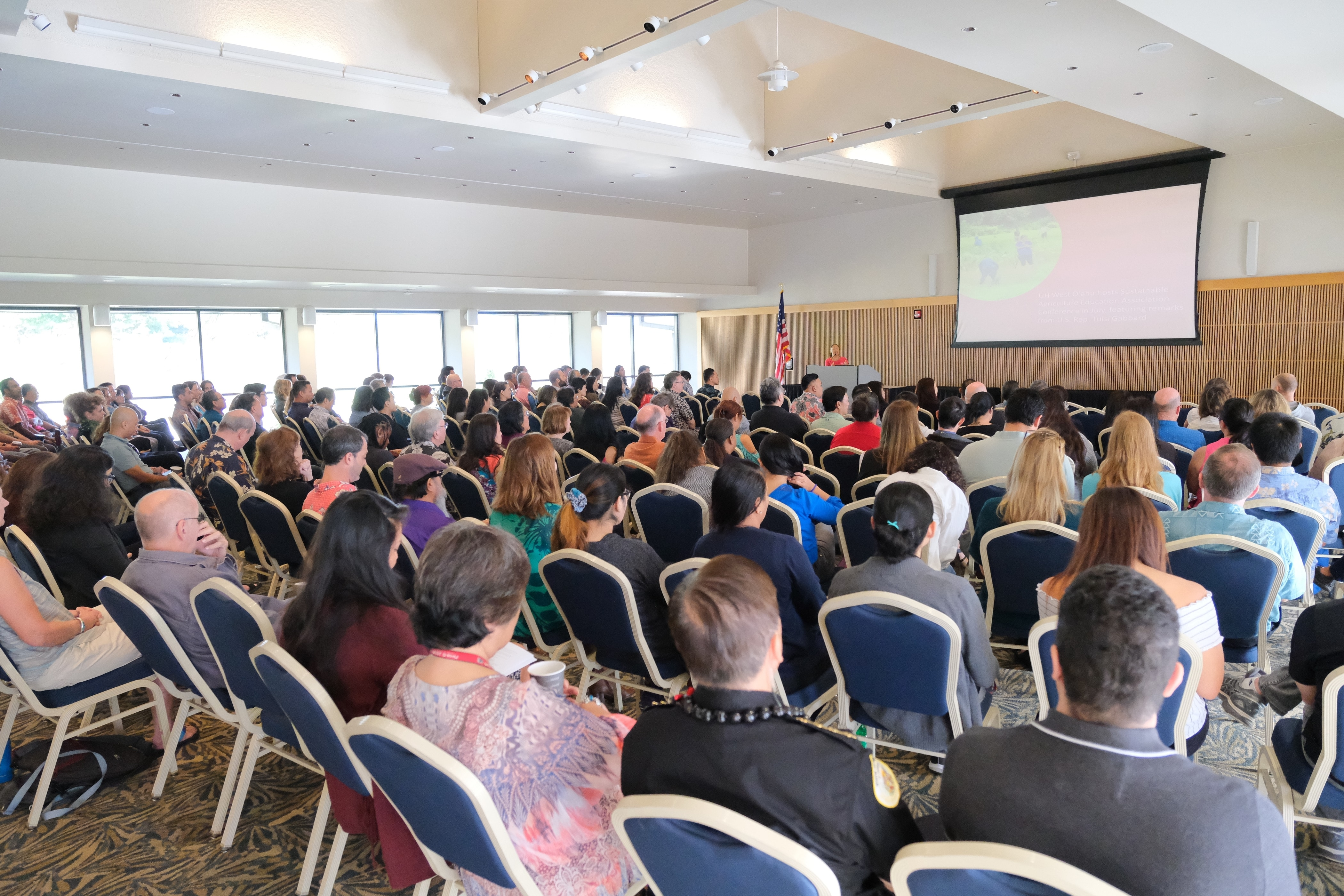 Photo of a large room filled with people sitting in rows of seats with large screen and speakers podium at front of room
