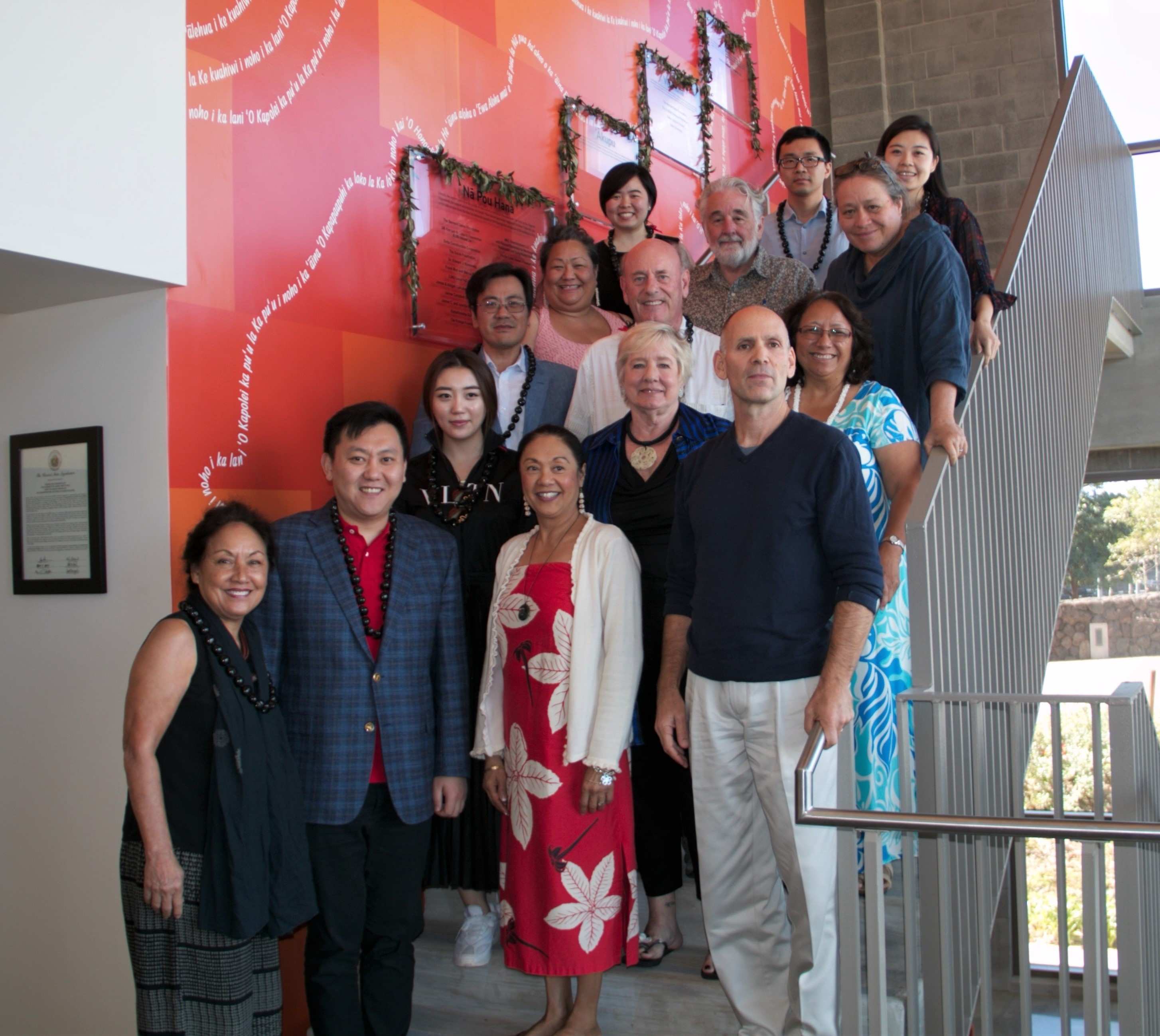 Photo of 14 people standing on stairs in front of an orange wall