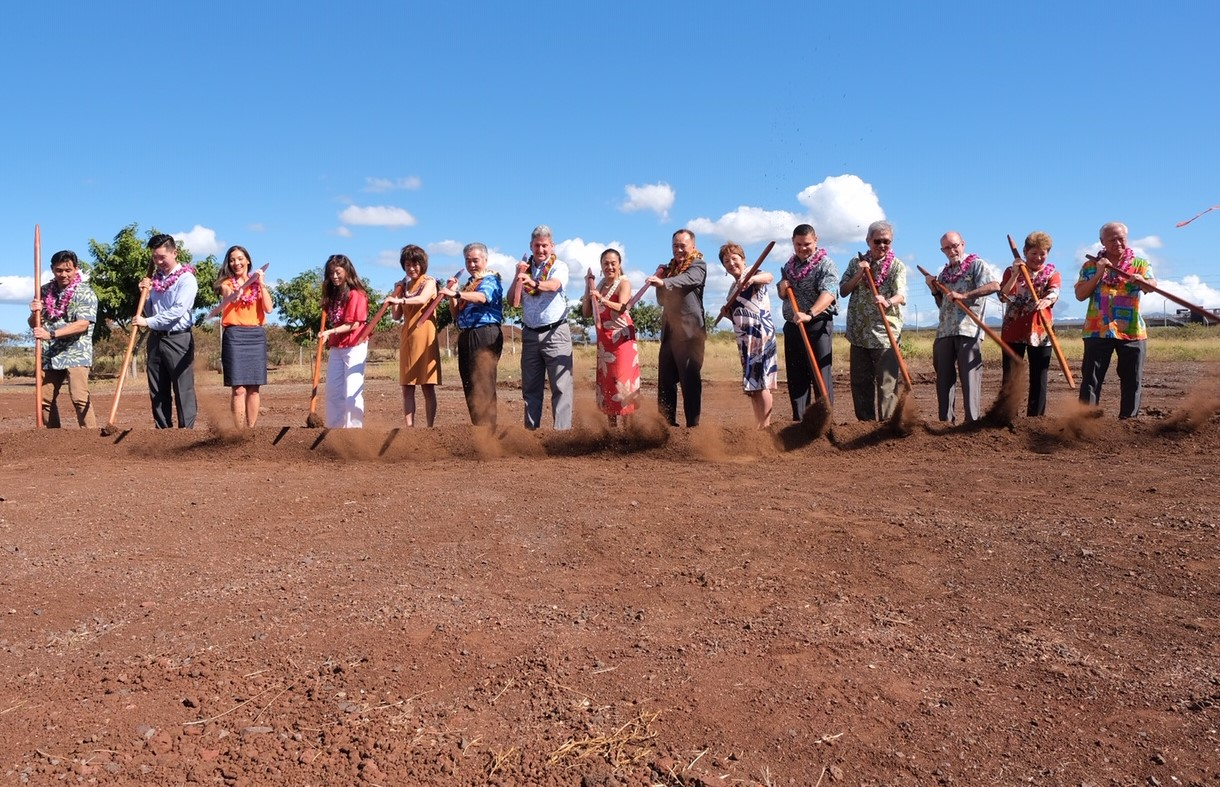 Photo of people in a line, digging in the ground with koa sticks