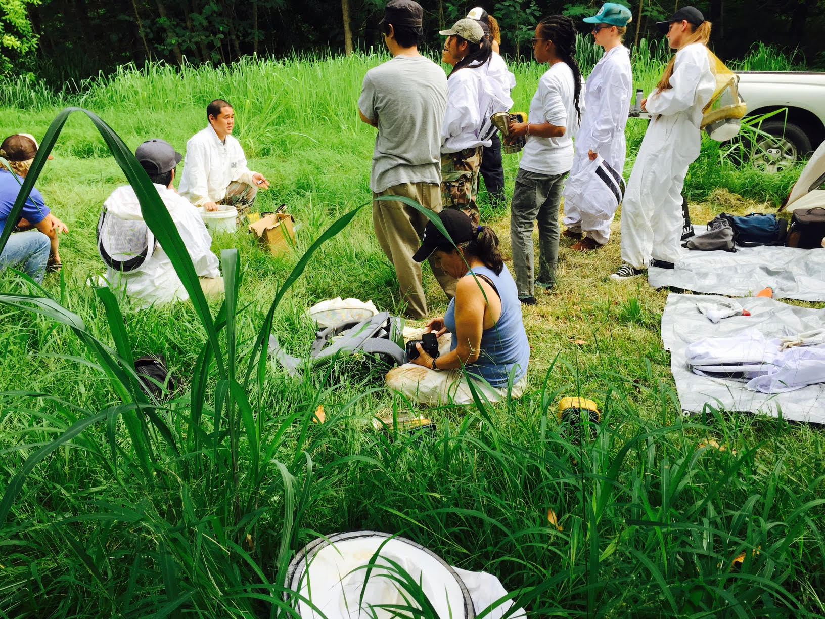 photo of an instructor and students outdoors. Students are mainly standing, dressed in Bee Keeper suits and an instructor is kneeling, talking to them.