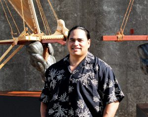 Photo of the artist Kupihea standing in front of two sculptures