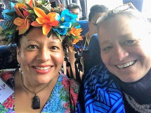 Selfie of showing two women - woman on the left is wearing a floral haku both are smiling in this slightly overexposed photo