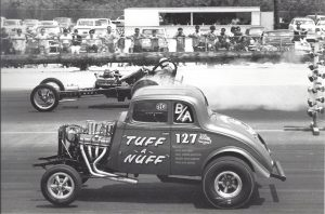 Black and White photo of two cars at a drag strip at the start of the race