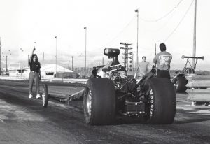 Black and white photo of a dragster at Hawaii Raceway Park. Three people are in the photo, including a woman gesturing with her arm as she walks toward the dragster