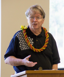 Photo of a man speaking at a lectern. He is wearing a black shirt and has a green and orange lei draped on his shoulders.