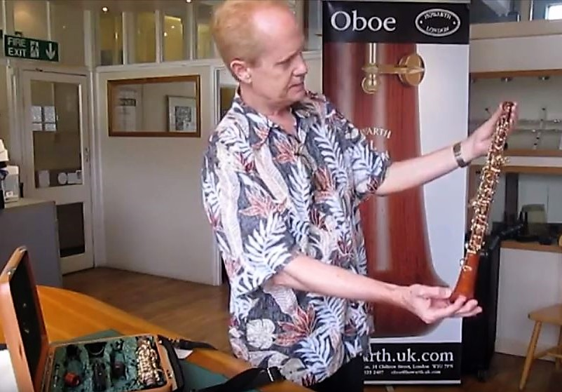Photo of a man standing in a room studying an oboe. He is wearing an Aloha Shirt; on the table in front of him is the case for the oboe, which is brown and has gold-colored keys. Behind the man and partially obscured is a sign that says Oboe and Howarth