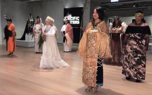 A screen grab from the film Pacific Sisters showing several women dressed in indigenous fashion standing in an art gallery