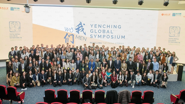 "A photo of what appears to be a couple hundred people standing on a stage. The screen in back of them says ""Yenching Global Symposium"""