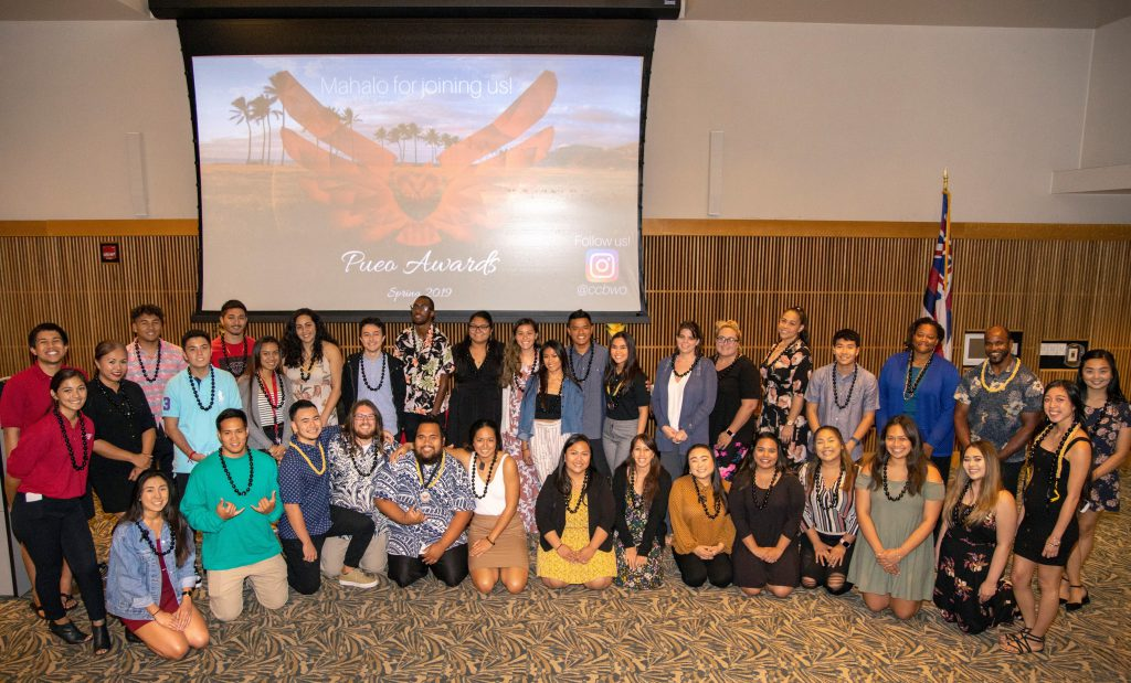 Photo of a large group of students, some wearing kukui nut leis, standing and kneeling for a group photo