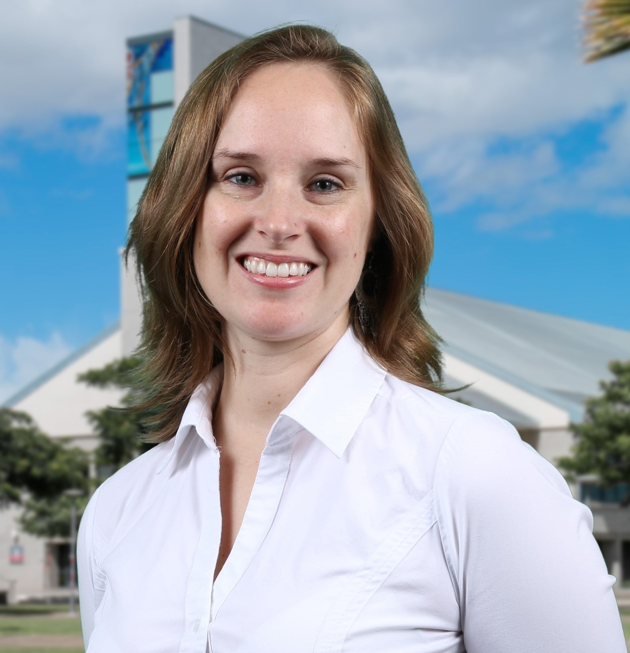 Portrait photo of Dr. Jennifer Byrnes. She is wearing a white blouse and smiling. The backdrop is the UH West Oahu library building.